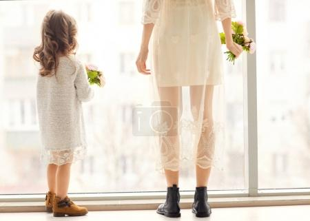 Mother and daughter have fun standing near a huge window, the daughter gives her mother flowers on her mother's day.