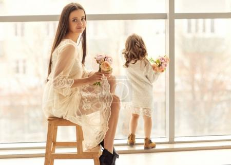 Photo for Mother and daughter have fun standing near a huge window, the daughter gives her mother flowers on her mother's day. - Royalty Free Image