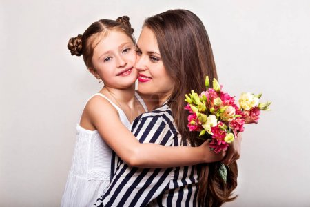 Photo for Daughter gives flowers to her mother on her mother's day - Royalty Free Image