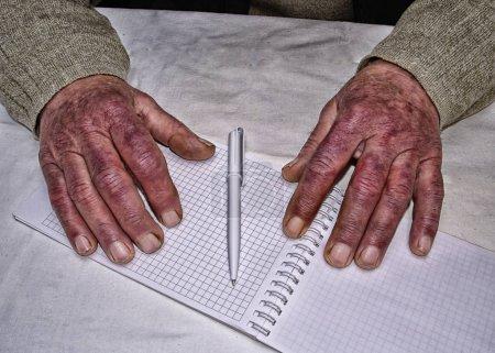 Photo pour Gros plan des mains ridées d'un vieil homme caucasien tenant un stylo et du papier, portant un pull vert - image libre de droit