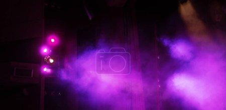 Photo pour Feux de scène. Contexte dans le spectacle. Projecteur lumineux dans l'obscurité. L'intérieur de la scène théâtrale est éclairé par le projecteur. Lumières de scène et fumée de scène pendant le concert - image libre de droit