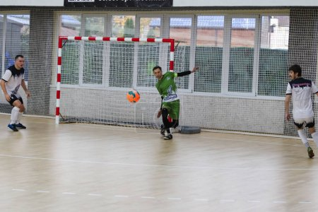 Photo for Odessa, Ukraine - October 11, 2019: Unidentified local team players play indoor soccer futsal tournament on the parquet floor. The right moment of sports soccer game in an indoor hall, indoor soccer - Royalty Free Image