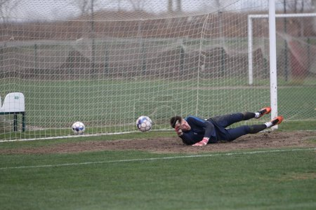 Photo for ODESSA, UKRAINE - CIRCA 2019: A goalkeeper of a local football team makes a save while playing in a regional derby championship on a bad football field. Soccer goal, goal net - Royalty Free Image