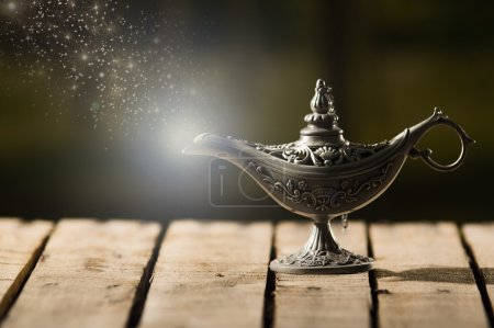 Photo for Beautiful antique metal lamp in true Aladin style, animated star dust coming out, sitting on wooden surface. - Royalty Free Image
