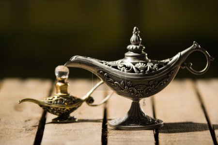 Photo for Beautiful antique metal lamp in true Aladin style, smaller model placed next to it, sitting on wooden surface. - Royalty Free Image