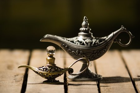 Beautiful antique metal lamp in true Aladin style, smaller model placed next to it, sitting on wooden surface