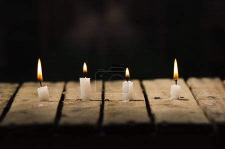 Photo for Four white wax candles sitting on wooden surface burning with black background, beautiful light setting. - Royalty Free Image