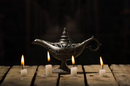 Photo for Four white wax candles sitting on wooden surface burning, Aladin style lamp placed behind, black background. - Royalty Free Image