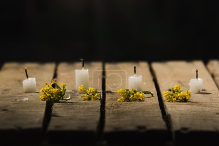 Photo for Four white wax candles sitting on wooden surface, no flames burning, with black background, beautiful light setting. - Royalty Free Image