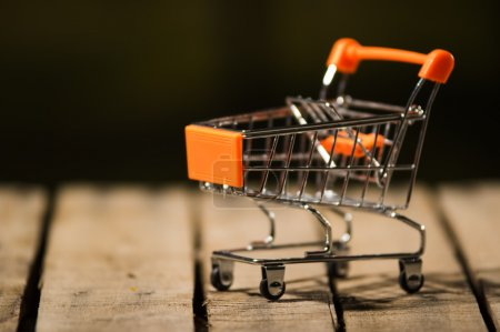 Photo for Miniature shopping trolley sitting on wooden surface, magicians concept. - Royalty Free Image