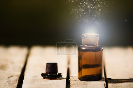 Photo for Small brown medicine bottle for magicians remedy, animated star dust coming out from top ,sitting on wooden surface. - Royalty Free Image