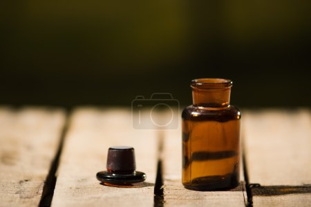 Photo for Small brown medicine bottle for magicians remedy, black cap lying next to it on wooden surface. - Royalty Free Image