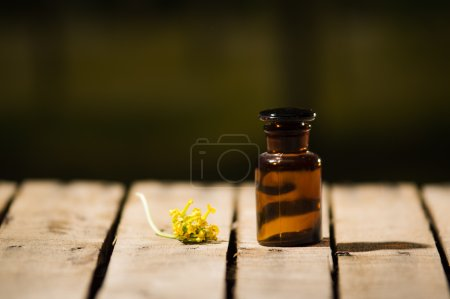 Photo for Small brown medicine bottle for magicians remedy, yellow flower lying next to it, sitting on wooden surface. - Royalty Free Image