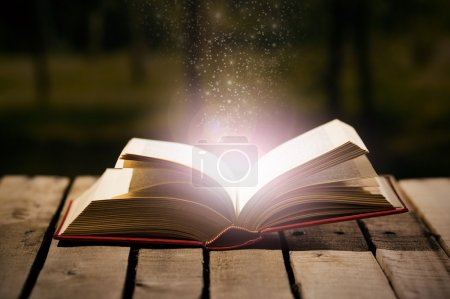 Photo for Thick book lying open on wooden surface, magic star dust coming out of it, beautiful night light setting, magician concept shoot. - Royalty Free Image
