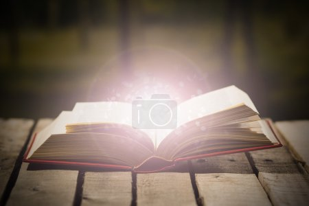 Photo for Thick book lying open on wooden surface, glowing animated star dust coming out, beautiful night light setting, magic concept shoot. - Royalty Free Image