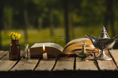 Photo for Thick book lying open on wooden surface, small brown bottle with flowers, Aladin style lamps and wax candle next to it, magic concept shoot. - Royalty Free Image