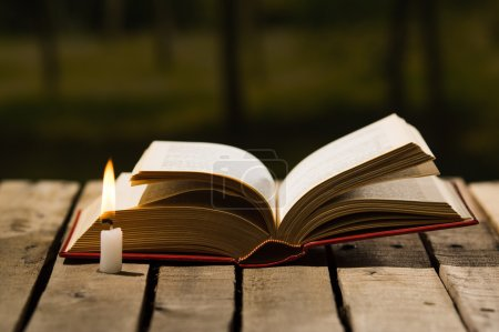 Photo for Thick book lying open on wooden surface, wax candle sitting next to it, beautiful night light setting, magic concept shoot. - Royalty Free Image