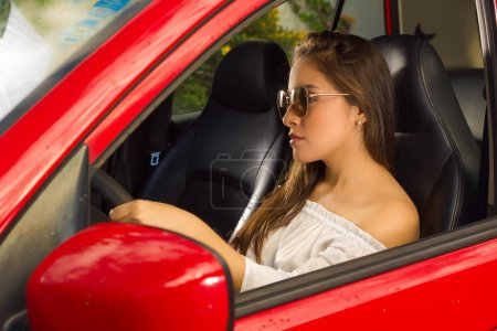Sexy woman wearing sunglasses and driving her red car