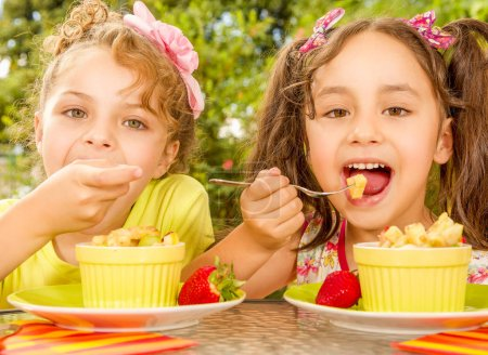 Two beautiful young girls, eating a healthy pineaple and grapes using a fork, in a garden background