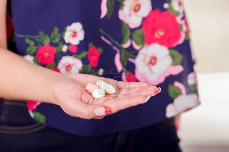 Close up of a woman hand, holding in her open hand a soft gelatin vaginal tablet or suppository, treatment of diseases of the reproductive organs of women and prevention of womens health