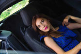 Close up of beautiful woman wearing a blue dress in a reclined seat and posing inside of a luxury black car on a roadtrip, the car standing on the sidelines, in a blurred nature background