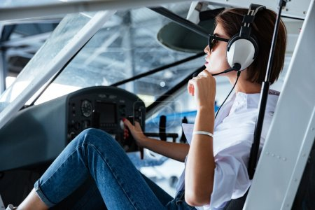 Woman pilot sitting and talking with headset in small plane
