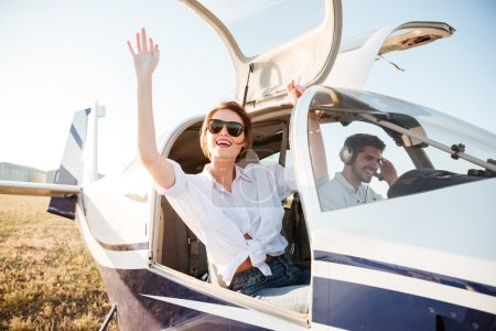 Woman in sunglasses waving from the plane cabin after landing