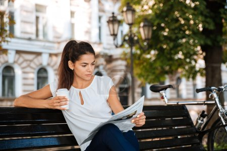 Woman reading newspaper while sitting on the bench