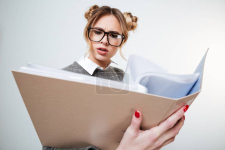 Serious frowning young woman in glasses reading documents in folder