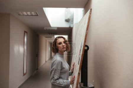 Young woman holding canvas on the easel