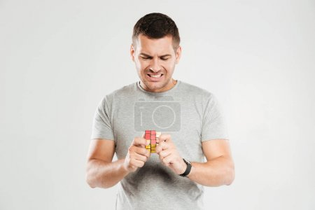 Confused man try to solve Rubik's cube.