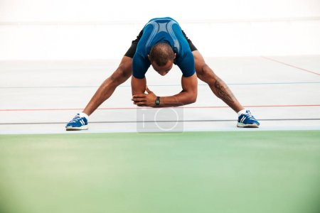 Full length portrait of a young sportsman doing stretching