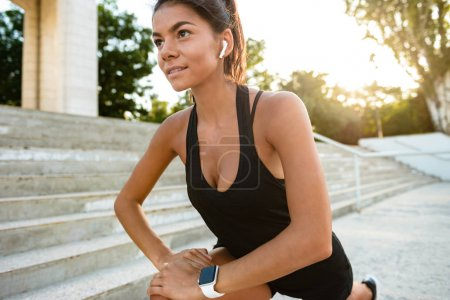 Portrait of a young fitness woman in earphones