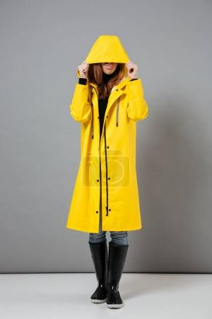 Full length portrait of a young girl dressed in raincoat