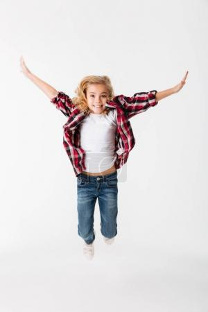 Full length portrait of a cheerful little girl jumping