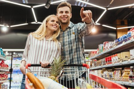 Happy smiling couple with a trolley shopping