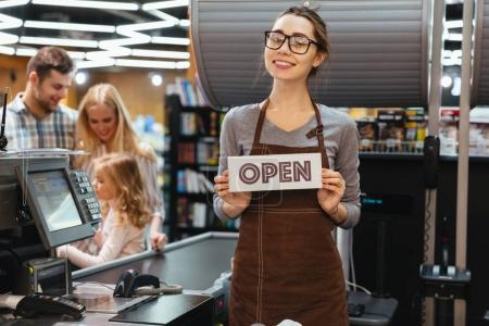 Portrait of friendly woman cashier holding open sign