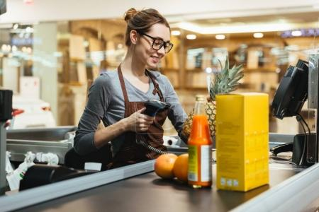 Smiling female cashier scanning grocery items