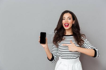 Photo pour Portrait d'une femme joyeuse pointant du doigt un téléphone portable à écran vierge isolé sur fond gris - image libre de droit
