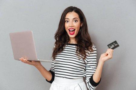 Porträt einer aufgeregten Frau mit Laptop