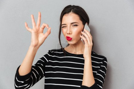 Photo for Portrait of a pretty woman talking on mobile phone and showing ok gesture isolated over gray background - Royalty Free Image