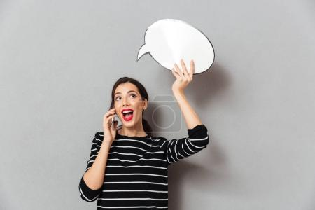 Portrait of a pretty woman holding blank speech bubble
