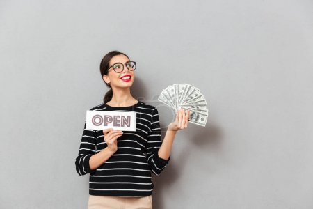Portrait of a satisfied woman in eyeglasses holding open sign