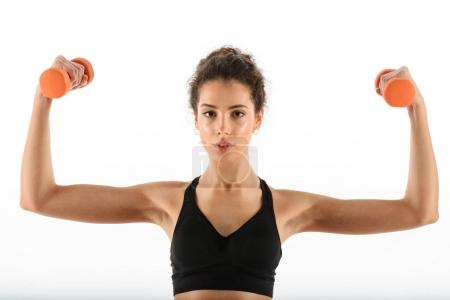 Calm curly brunette fitness woman doing exercise with dumbbells