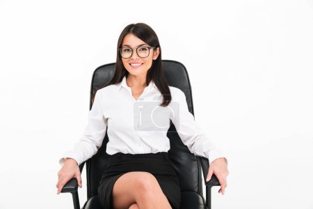 Photo for Portrait of a happy asian businesswoman in eyeglasses sitting in an office chair isolated over white background - Royalty Free Image