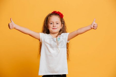 Little girl child standing isolated showing thumbs up.