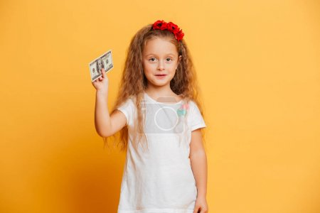 Little cute girl standing isolated holding money looking camera.