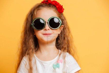 Photo pour Image de petite fille souriante mignonne debout isolé sur fond jaune portant des lunettes de soleil regardant caméra . - image libre de droit