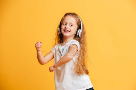 Cheerful girl dancing isolated listening music with headphones.