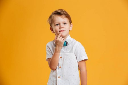 Little boy child standing isolated over yellow